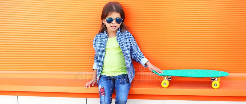 stylish-little-girl-child-sitting-skateboard-wearing-sunglasses-checkered-shirt-over-orange-background-65574739-e1515587794496.jpg